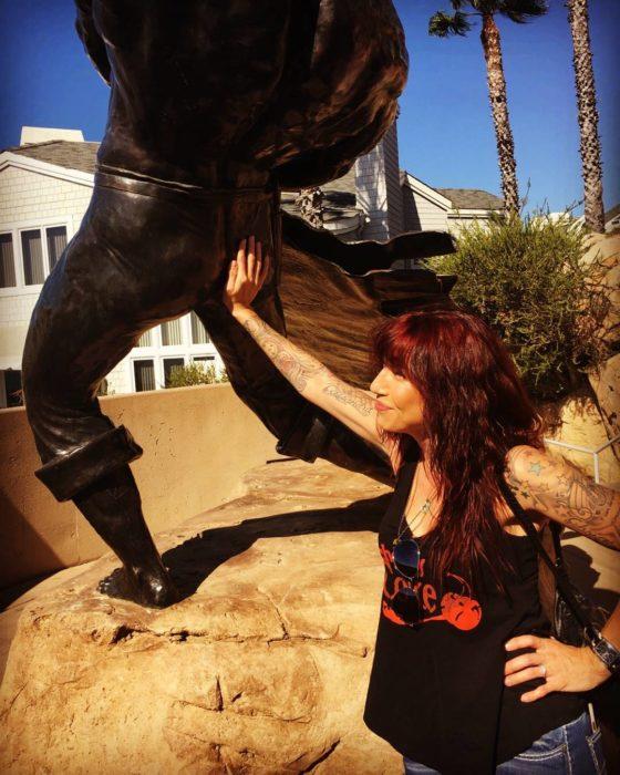 mujer toca el trasero de una estatua