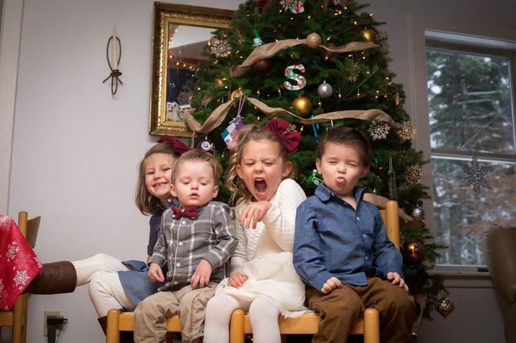 cuatro niños frente a un árbol de navidad