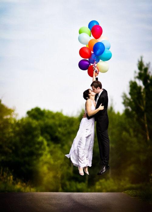 novios besándose sostenidos de globos de colores