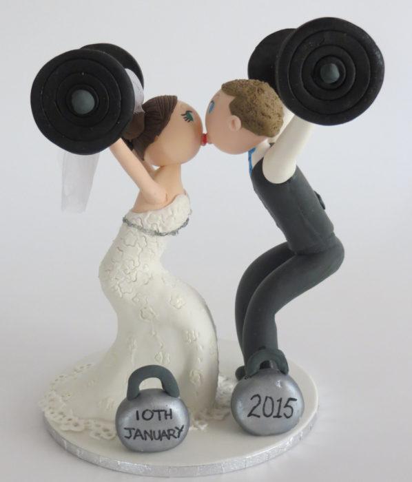 muñecos de pastel de bodas levantando pesas