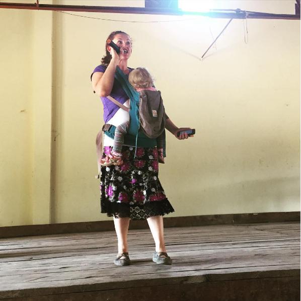 señora con un bebé da una conferencia