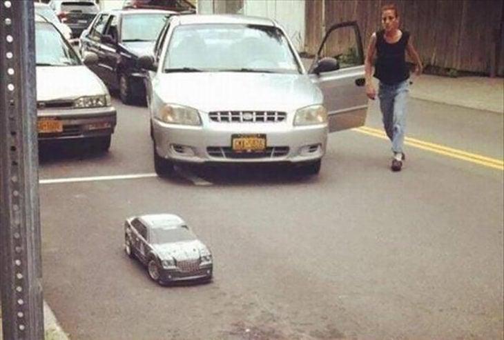 carro de juguete estacionado en lugar para carro real, mujer molesta