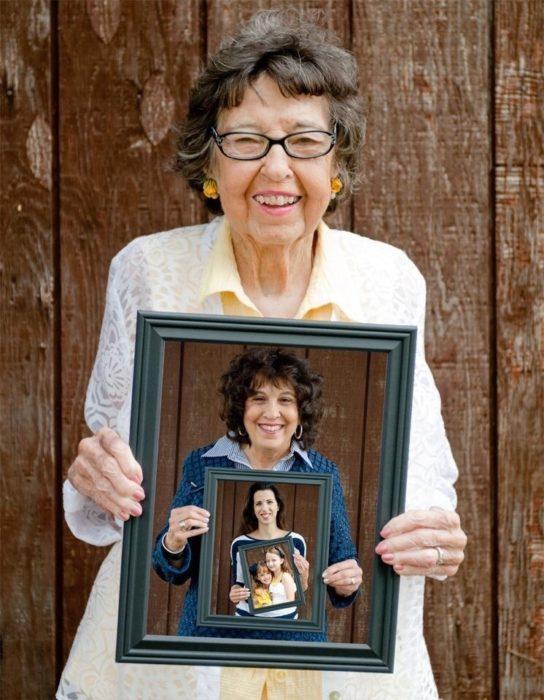mujer sostiene un retrato de su hija que a la vez sostiene un retrato de su hija