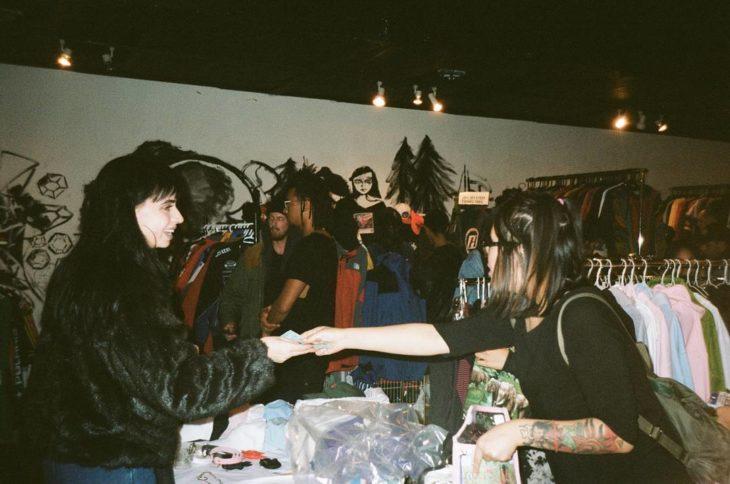 mujer pagando a comerciante en un mercado