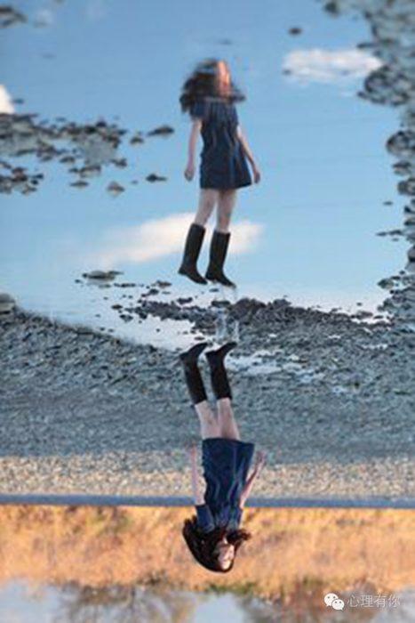 reflejo de niña saltando en un charco
