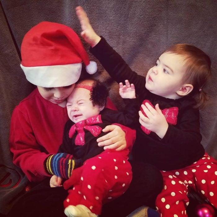 tres hermanitos se toman foto de navidad
