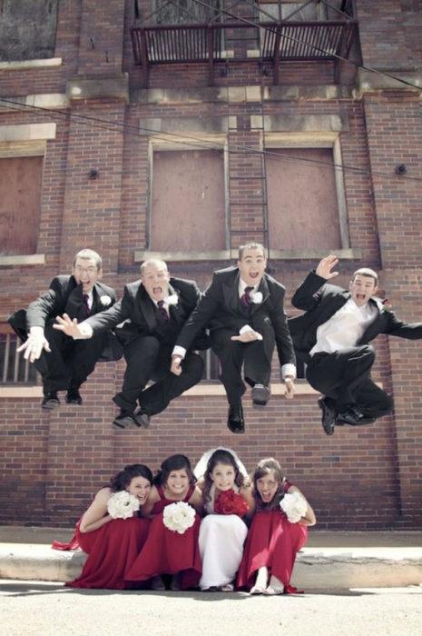 foto de invitados del novio saltando sobre las damas