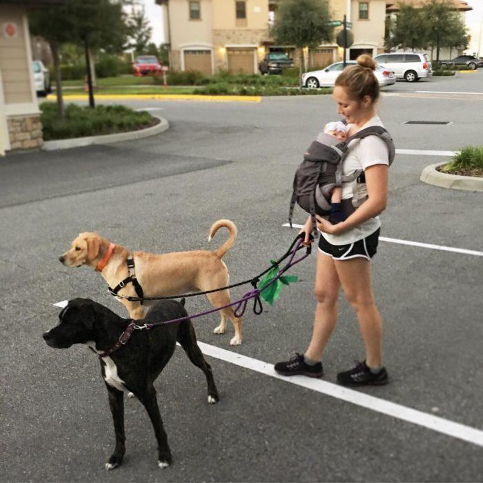 mujer cargando bebé caminando con perros
