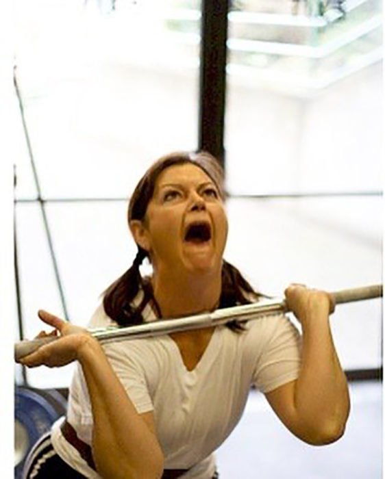 mujer con gesto gracioso levanta pesas