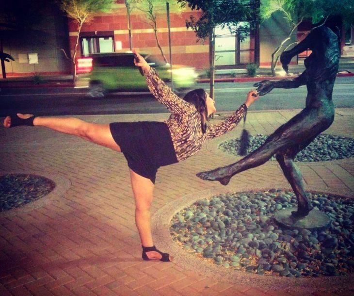 mujer posa con estatua de bailarín