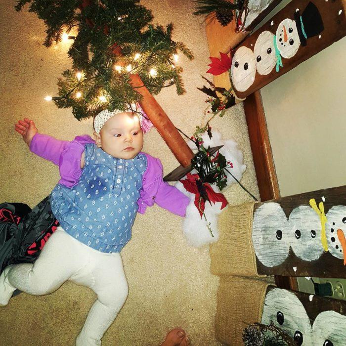niña en el suelo con árbol de navidad tirado cerca de su cabeza