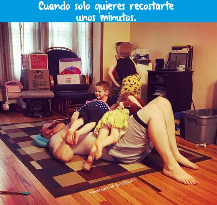 hombre recostado en la sala con sus hijos encima
