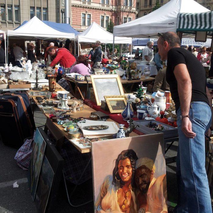 persona mirando cuadros de madera en un mercado ambulante