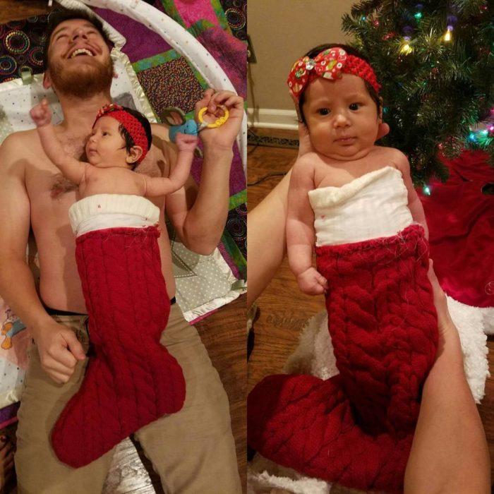 apá sostiene a bebé dentro de calcetín navideño