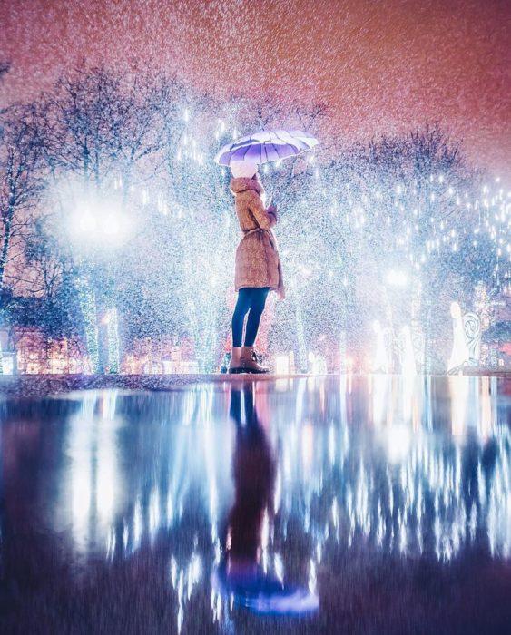 mujer con sombrilla en una pista de hielo