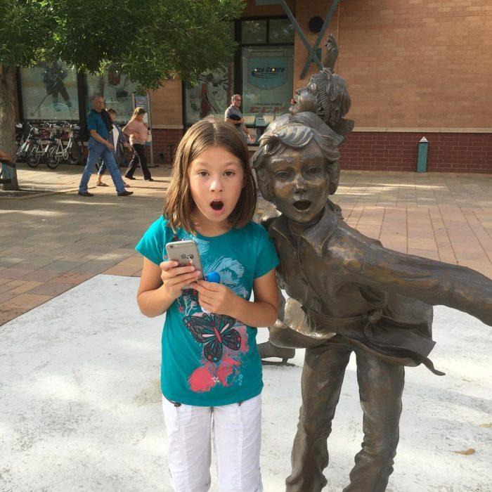 niña con expresión de sorpresa posa con estatua con expresión de sorpresa