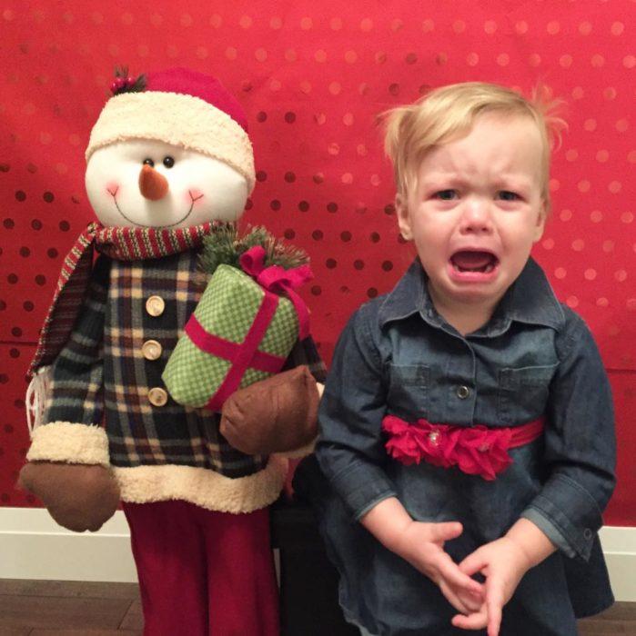 niño llorando al lado de un muñeco navideño
