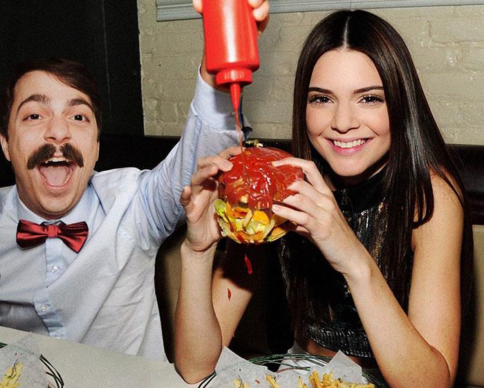 hombre se edita al lado de kendall jenner poniendo condimentos a su hamburguesa