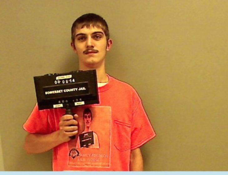 hombre detenido usa camiseta anaranjada con la foto de él detenido