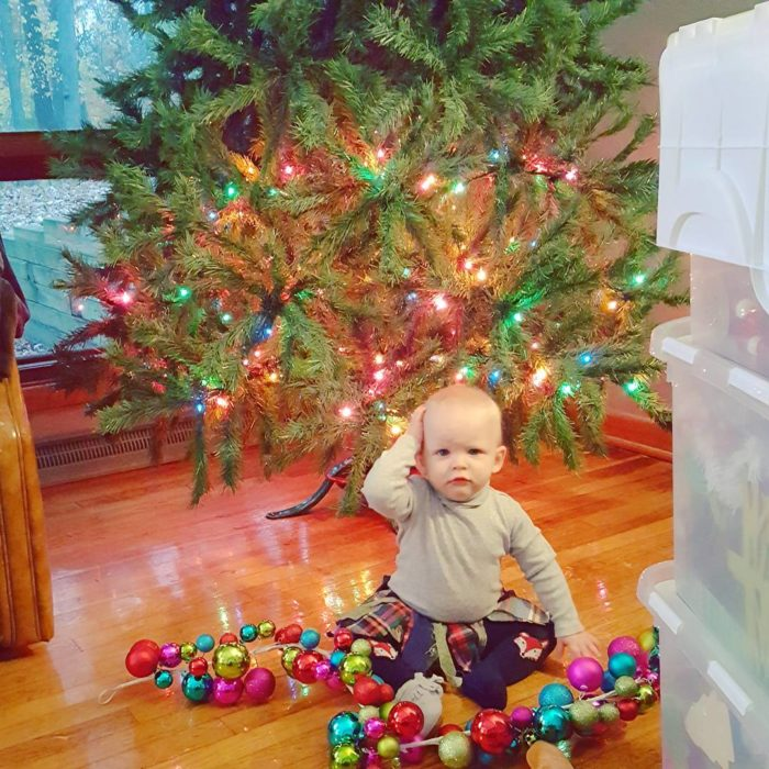 niño en el suelo frente a árboil navideño y con esferas navideñas en el suelo