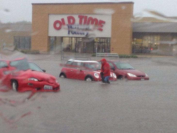 carros frente a un centro comercial inundado
