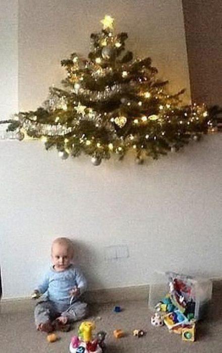 bebé al aldo d eun árbol de navidad en la pared