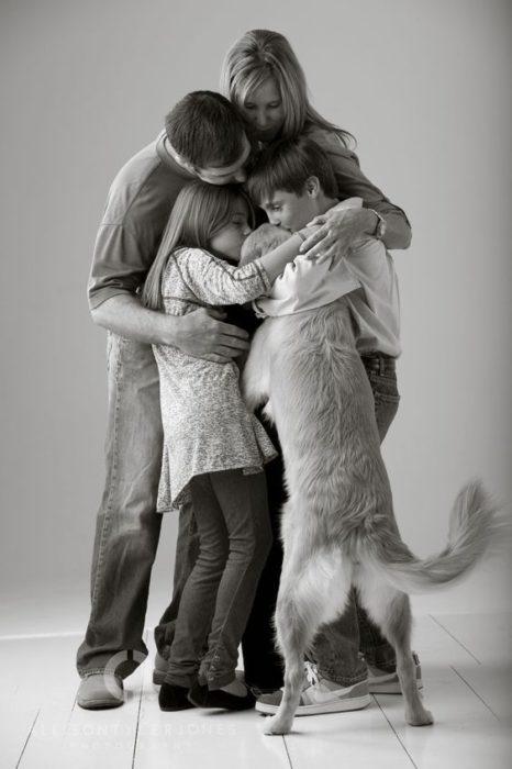 familia abrazando a un perro
