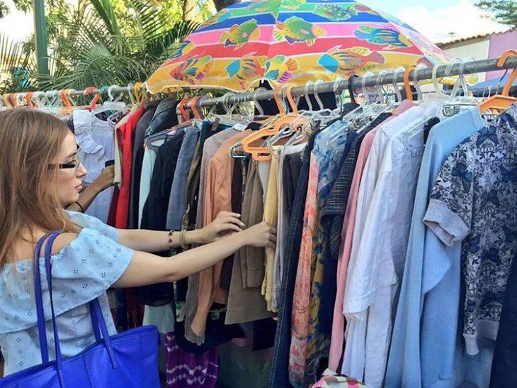 mujer hurgando ropa en un tianguis