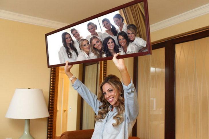 Novia sosteniendo un espejo en el que se muestran las damas de honor