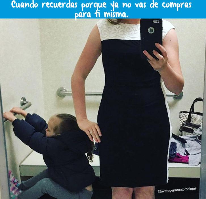 mujer probándose un vestido con su hija al lado