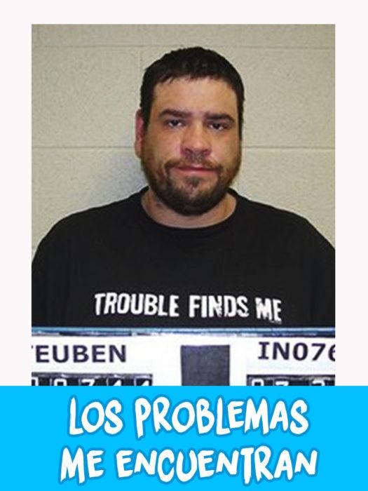 hombre detenido con camiseta que dice que los problemas lo encuentran