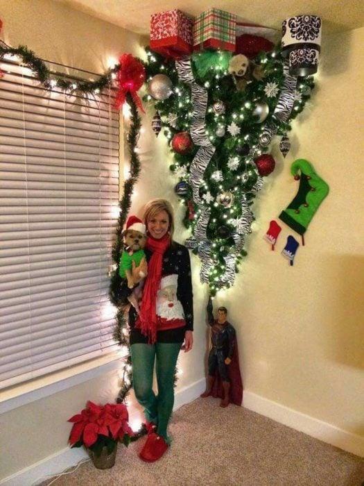 mujer posa con su perro al lado de árbol de navidad puesto de cabeza