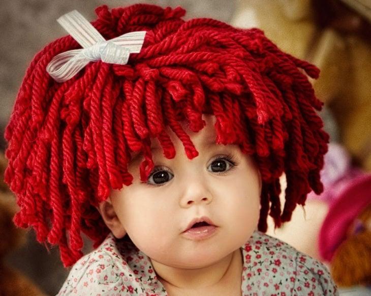 niña con peluca de estambre roja
