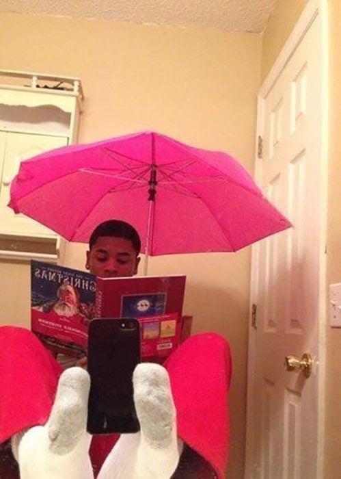 muchacho leyendo un libro con un paraguas rosa se toma selfie con los pies