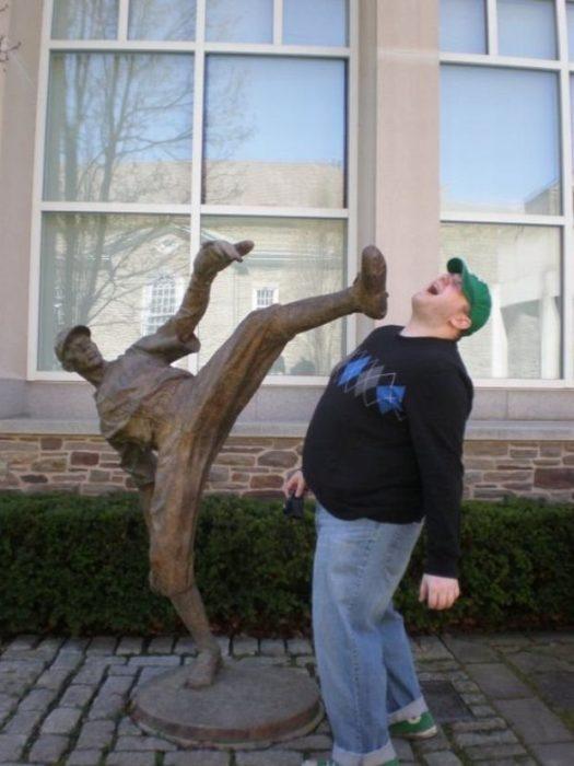 hombre posa al lado de una estatua que lanza una patada