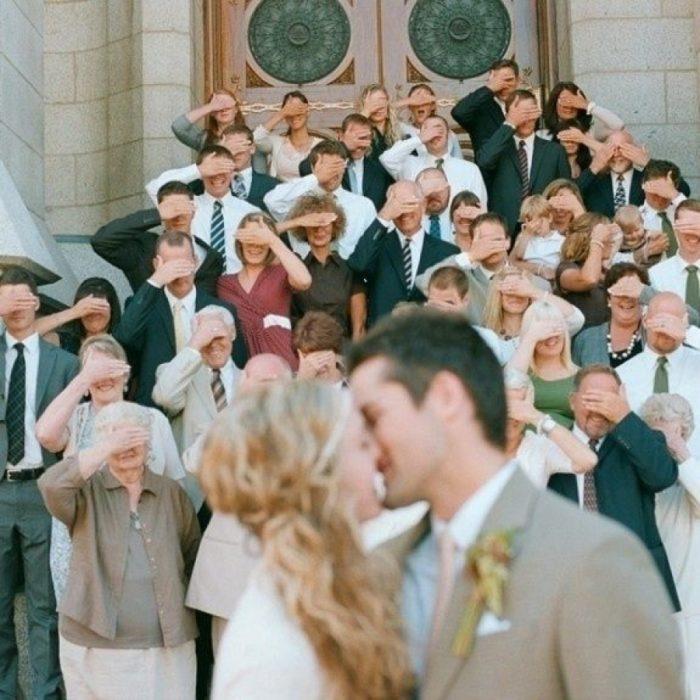 invitados tapándose los ojos mientras los novios se vesan