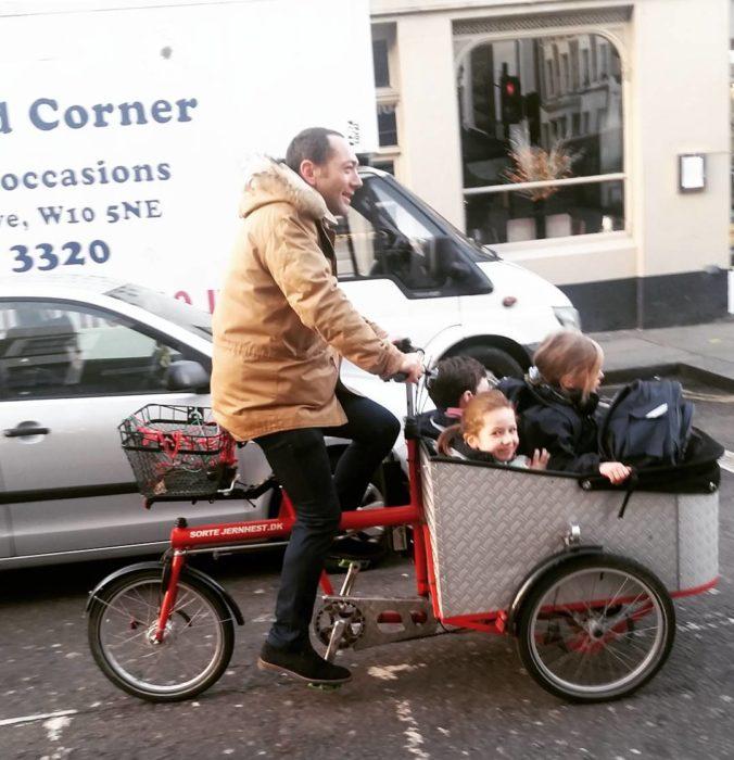 niños en una bicicleta que maneja su papá