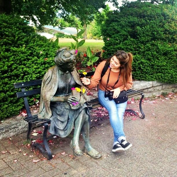 muchacha sostiene una flor al lado de una estatua de anciana