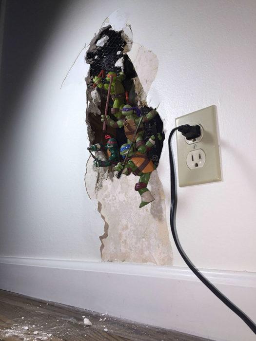 juguetes de tortugas ninja en agujero de pared