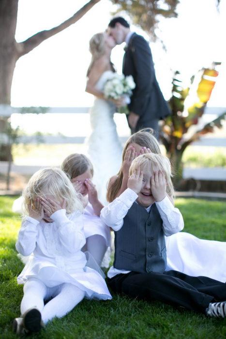niños se tapan los ojos mientras unos novios se besan