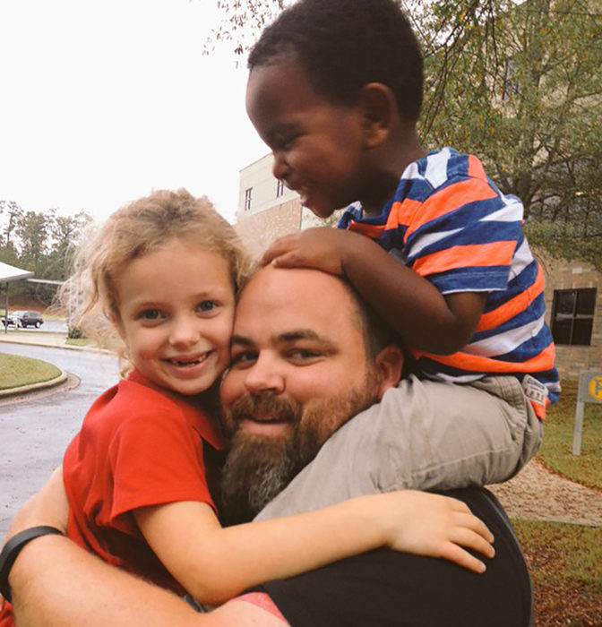 hombre cargando a su hija e hijo adoptivo