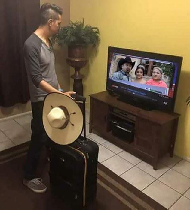 hombre con una maleta mirando el tv