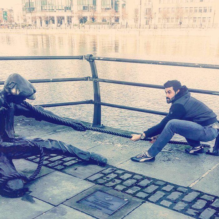 hombre posa al lado de estatua de hombrecillo que tira de una cuerda