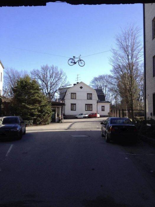 casa, a unos metros una bicicleta está colgada en un lazo