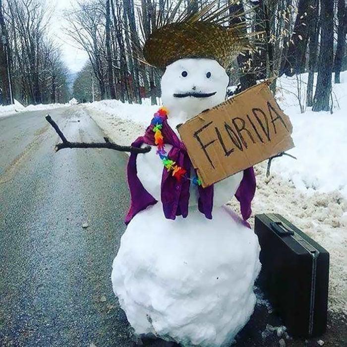 mueco de nieve en carretera con un cartel que dice Florida