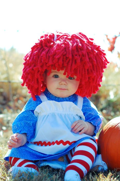 niña vestida de muñeca con peluca de estambre