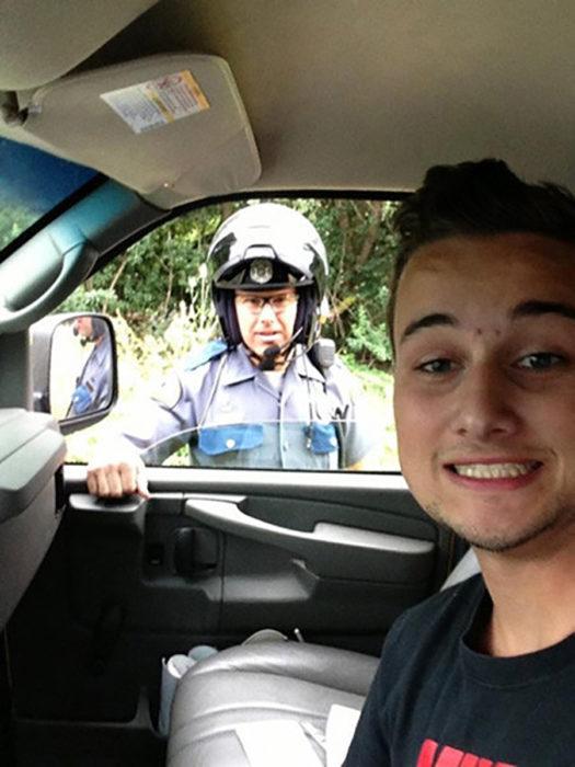 muchacho en carro se toma foto con un oficial