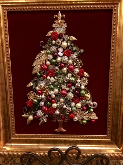 joyería acomodada como árbol de navidad dentro de un marco de foto