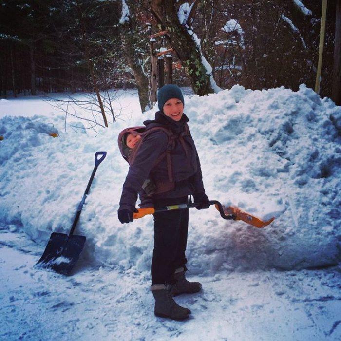 mujer con bebé cargado en la espalda y pala en la nieve