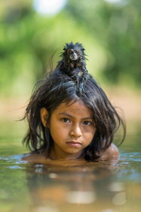 primate sobre la cabeza de una niña en un río